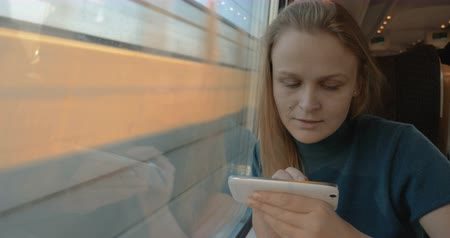 podróżnik : Female traveler in the train using pen to type sms on cell phone or surf in the Internet. Sometimes she looking out the window