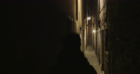 uliczka : Steadicam shot of a woman with phone running at night. She escaping from maniac in dark narrow passage between old worn buildings