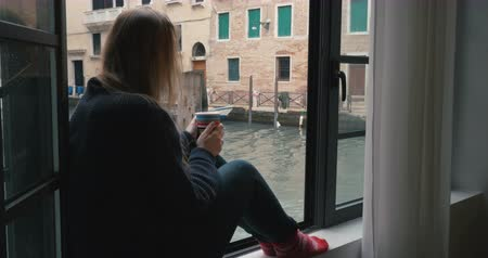 wistful : Woman sitting on the windowsill and having hot coffee. Venice canal and old worn buildings outside, boat sailing by Stock Footage