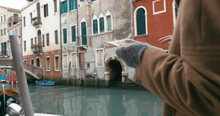 veneza : Steadicam shot of a woman with touch pad having a nice walk in Venice. She going along the canal with old worn buildings in Venice