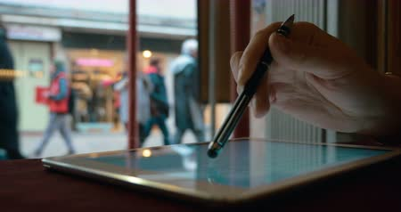 таблетка : Close-up shot of female hand typing on tablet computer with pen. Woman using device in cafe by the window with street view