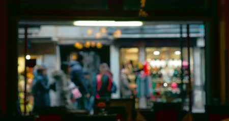 restoran : Defocused shot of people walking by the restaurant show window. Video is made inside the restaurant.