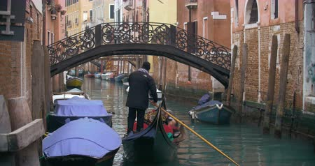 vyhlídkové : Gondola with people sailing along the narrow canal in Venice and coming up to the bridge. Traditional way of city sightseeing