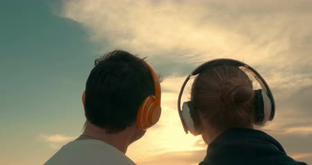 созерцать : Steadicam shot of man and woman listening to the music in headphones and watching at the rising or setting sun, their backs are turned towards the camera.