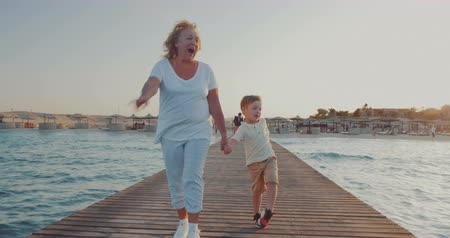 бабушка : Steadicam shot of a grandmother walking with little grandchild along the wooden pier on resort. They holding hands, woman talking to the boy and they looking at sea