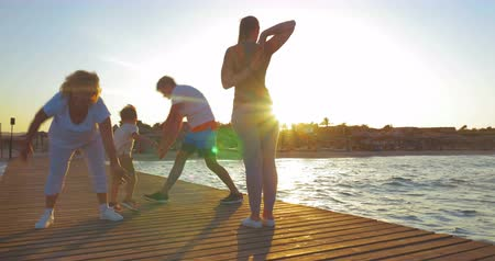 güneş ışını : Steadicam shot of family on the pier at sunset. Parents and grandmother doing physical exercises, little boy playing and jumping nearby