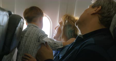 paper airplane : Little boy sitting on grandmothers lap and looking out plane window, grandfather trying to entertain him with paper plane. Family travel by air