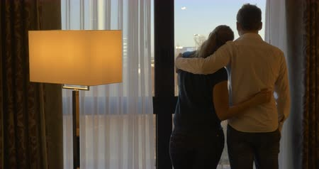 отель : Back view of romantic couple at home or in hotel room. Woman opening the curtain, they embracing gently and looking out the window. Happy time together Стоковые видеозаписи