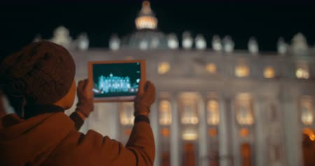 catedral : Night view of St. Peters Basilica in Vatican City. Female tourist using tablet PC to take some photos of famous Catholic church, bright example of Renaissance architecture