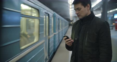 smartfon : Young man using smart phone to type text message at the underground station, train passing by. Everyday traveling by public transport