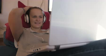 dívat se : Steadicam shot of a laughing woman in earphones with laptop on the sofa. She watching comedy film or listening funny story during video chat