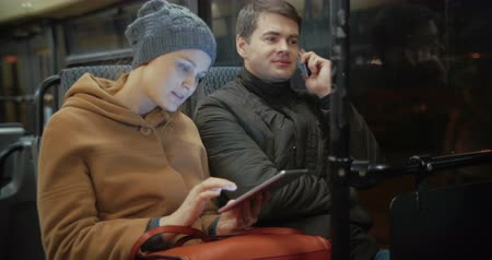 večer : Young people in the bus. Woman uisng tablet PC and man talking on the phone during evening traveling in the city
