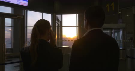 bizneswoman : Young businesspeople at the airport terminal. Woman having a phone talk, man looking out the window and enjoying sunset scene Wideo