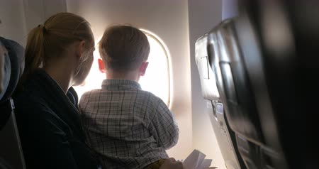 points of interest : Son sitting on mothers lap in plane and they enjoying view from illuminator, mom kissing the boy and telling something to him Stock Footage