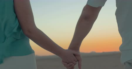 drží se za ruce : Close-up shot of man and woman taking hands during sunset on the beach. They meant to be together Dostupné videozáznamy