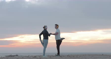 vezeték nélküli : Young man and woman in wireless headphones doing physical exercises on the beach at sunset