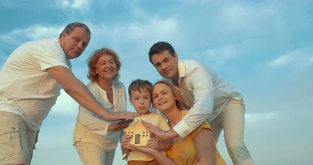 biztosítás : Steadicam shot of big family with small wooden house. Boy holding it and they all protecting it with hands. Family hearth or insurance concept