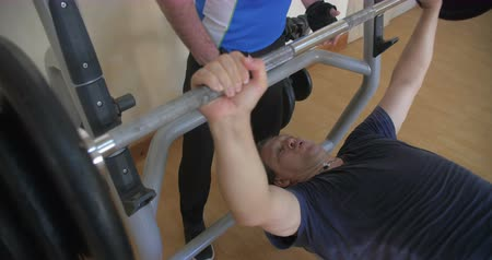 safe workout : Strength training with gym instructor. Mature man doing chest press exercise with personal trainer