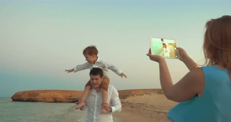 omuzlar : Little son riding on fathers neck and imitating plane while walking on the beach. Mother using touch pad to take family vacation photos