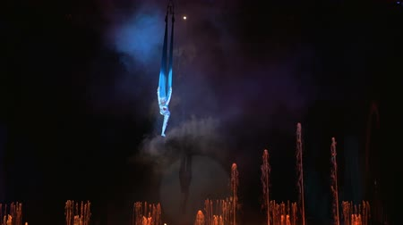 цирк : Woman gymnast performing on aerial silk on background of dancing fountains. Elegant aerial dance