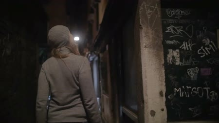 noite : Slow motion steadicam shot of a woman walking along the alleyway with dim light. Night city with worn grungy buildings Vídeos