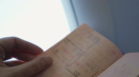 pas : Slow motion and close-up shot of woman looking through the passport with stamps. Traveling marks