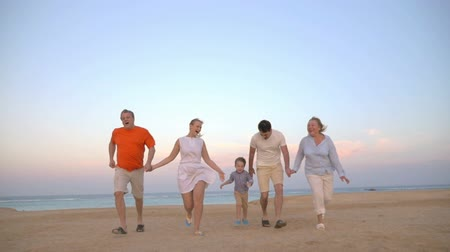 detém : Slow motion steadicam shot of a family of five holding hands and running on the beach. Happy vacation with fun