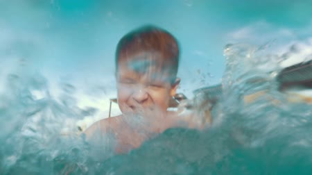 Slow motion of a child playing in the pool. Happy boy having fun on vacation. Close-up shot of water splashes 影像素材