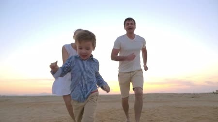 веселье : Slow motion steadicam shot of a playful little boy taking away parents hands and running away. Happy mother and father following him. Family fun on vacation