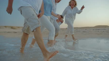 Slow motion steadicam, low angle shot of happy family with child having fun while splashing water with feet on the coast