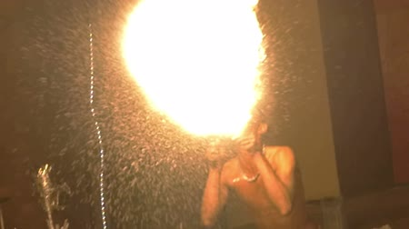 darkskinned : Slow motion shot of an episode of fire show. Dark-skinned artist breathe fire in the night.
