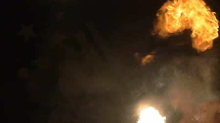 darkskinned : Slow motion shot of an episode of fire show. Dark-skinned artist blows fire with two torches in turns.