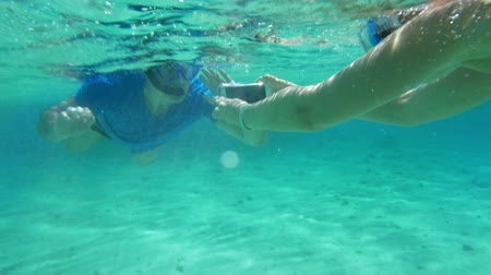 underwater video : Tourists diving with smartphone. Woman taking picture or shooting video of a man in snorkel underwater. Friendly diver waving with his hand