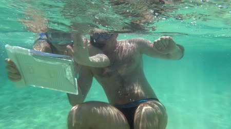 vodotěsný : Slow motion shot of a couple making selfie with tablet PC while snorkel diving.