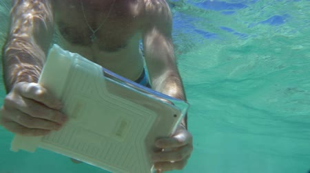 vodotěsný : Slow motion shoot of snorkelling young man. Hes shooting an underwater coral reef using tablet PC in waterproof case.