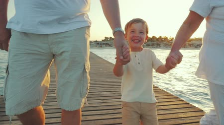 vacation : Slow motion steadicam shot of a little boy laughing and being happy during the evening walk on the pier with grandparents. Family vacation