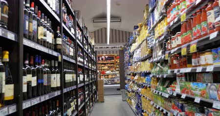 lojas : ROME, ITALY - FEBRUARY 13, 2015: Steadicam shot of moving forward in the store section with alcohol drinks and food products