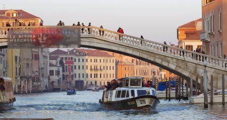 vyhlídkové : VENICE, ITALY - FEBRUARY 17, 2015: Water trams and boats sailing under the bridge with people walking there. Sightseeing of old Italian city