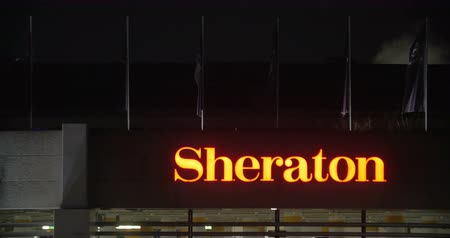 sheraton : DUSSELDORF, GERMANY - FEBRUARY 15, 2015:  Illuminated hotel Sheraton sign at night with some flags fluttering over. One of the largest and oldest international hotel chains
