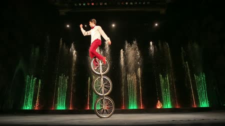 цирк : MOSCOW, RUSSIA - FEBRUARY 21, 2015:  Young man balancing on three wheeled cycle and doing tricks with plates. Exciting performance in the Circus of Dancing Fountains Aquamarine Стоковые видеозаписи