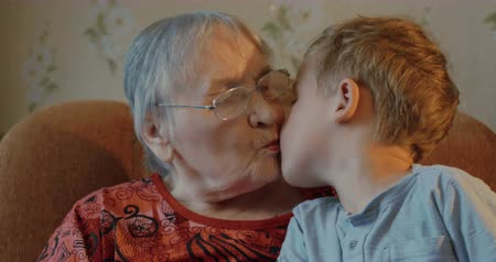 бабушка : Grandmother and grandson sit on the sofa, grandson sits on grandmothers knees, then he kisses her