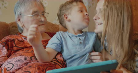 grandchild : Happy family use tablet sitting on the sofa at home, little boy kisses her grandmother and mother, mother kisses son in return