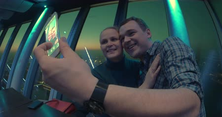 клуб : Happy couple taking selfie for smartphone being in night club or restaurant. Overlooking view of the night city is on the background.