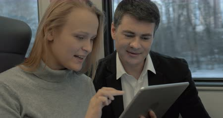 диалог : Man and woman are traveling by train. They are watching something in the tablet and having lively conversation. Стоковые видеозаписи