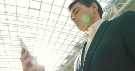 Low-angle shot of a young businessman using smartphone in modern building with glass roof. He39;s brightly lit with sunlight.