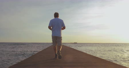 sport : Steadicam back shot of a mature man jogging along the wooden pier with following low angle shot of running feet against sea and sunset background. Sport on vacation