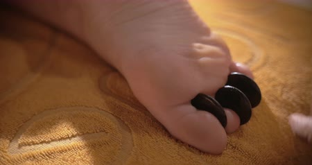 kamień : Closeup shot of a hot stone therapy for foot. Massagist is putting stones between toes.