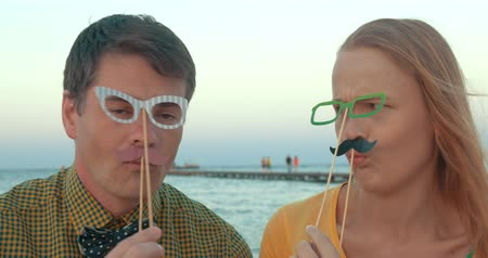 ostoba : Young man and woman with hipster style paper glasses and moustache having fun while making goofy faces outdoor by the sea. Trendy style