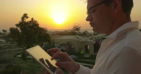 biznesmeni : Young man outdoor at sunset. He putting on glasses and starting to work with tablet computer. Business on vacation Wideo