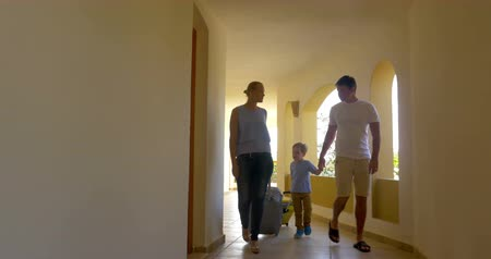 отель : Steadicam shot of a young parents and son walking with travel bags along the hotel corridor. Family arriving on vacation